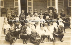 Milton Hershey with Hershey Industrial School students, seated on the steps of The Homestead. 1923