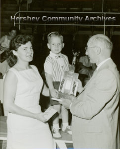 Hershey Park General Manager, George Bartels, presents the cutest baby award to Kyle Ann Katzenmoyer. 1956