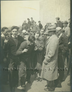 A wounded and bloody striker is helped through the crowd on the last day of the strike.