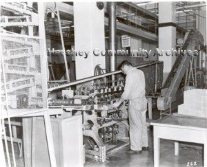 In 1956 Hershey Chocolate Corporation began manufacturing its own tins for Hershey's syrup. Here an employee monitors the progress of a can labeler. ca.1960-1970