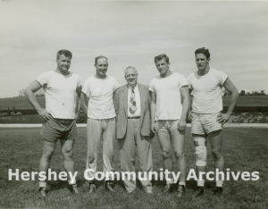 A group of players poses with Hershey Estates president, John B. Sollenberger. Left to Right: Mike Jarmoluk, tackle; Leroy Zimmerman, quarterback; Sollenberger; George Roman, tackle; Bob Davis, tackle, ca. 1949-1962