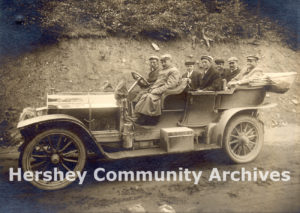 Milton Hershey and colleagues. Left to Right: Front Seat: Chauffeur, Milton Hershey; Second Seat: George Shearer (brother-in-law of Murrie), William Murrie; Third Seat: Ezra Hershey, C.V. Glynn, George Eppley, 1905