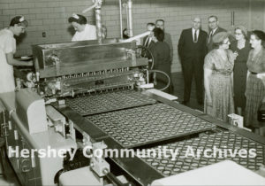 Guests watch employees work on the moulding line of the new Reese factory, November 30, 1957