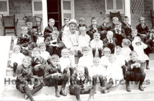 Milton Hershey surrounded by Hershey Industrial School students, seated on the steps of The Homestead, 1913