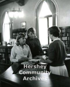 Librarian Irene Heaps assists two young patrons check out books, ca. 1965-1975