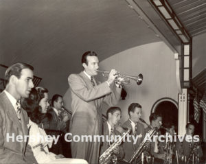 Vocalists Buddy DeVito and Kitty Kallen wait while band leader Harry James performs his trumpet solo at Hershey Park Ballroom, July 25, 1945