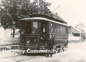 Conductor William Harper stands beside his Hershey trolley, ca. 1906