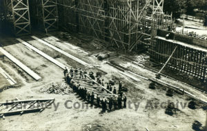 Over thirty men carry a single wooden support structure during the construction of the Arena, 1936.