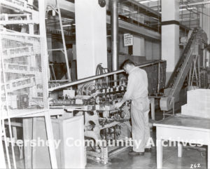In 1956 Hershey Chocolate Corporation began manufacturing its own tins for Hershey's syrup. Here an employee monitors the progress of a can labeler. ca. 1960-1970