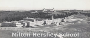 Hershey Industrial School Jr-Sr High School building sits atop Pat's Hill with the Hotel Hershey in the background, 1934